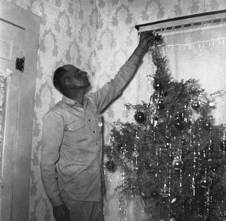 Man putting start on a Christmas Tree