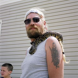 A Man With A Snake On His Shoulder