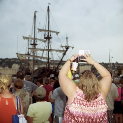 A Woman Takes A Smartphone Photo Of A Tall Ship
